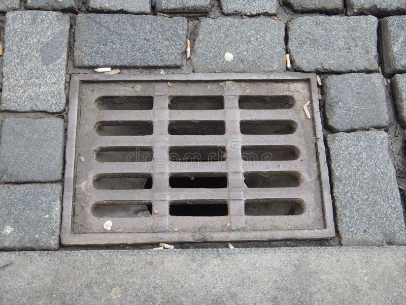 浇灌与栅格的排水设备孔在一条被修补的街道上 免版税库存图片