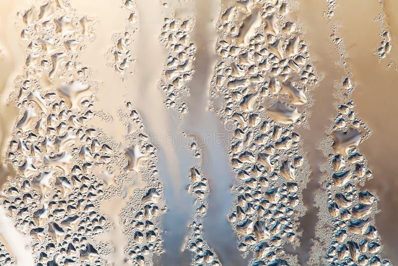 浇灌与泡影和小滴的下落在玻璃窗背景 抽象液体塑造宏观看法 浅深度  免版税库存图片