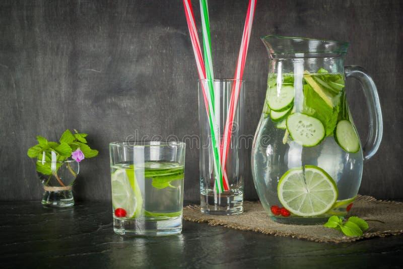 浇灌在一个玻璃瓶子和玻璃的戒毒所 新鲜的绿色薄菏和莓果 刷新和健康饮料 库存照片