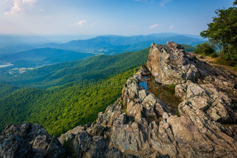 浇灌在小的石人被赶走的蓝色的峭壁和看法的水坑 免版税库存图片