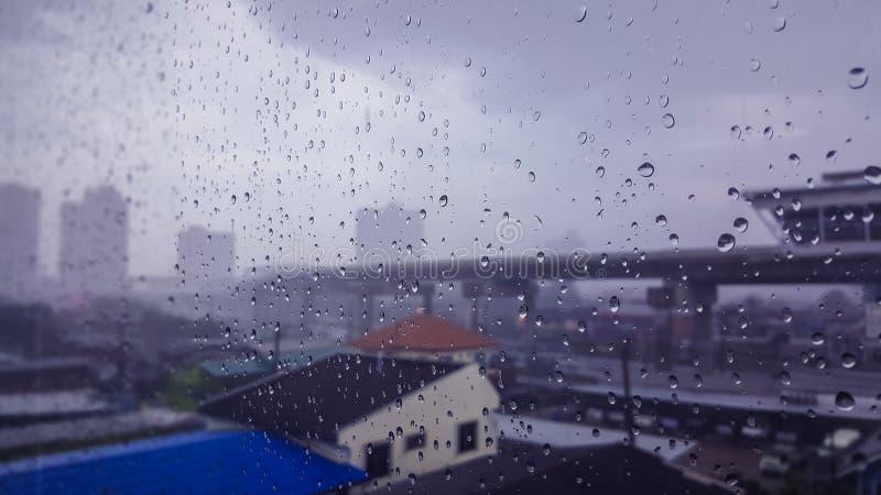 浇灌在杯的下落摩天大楼在一个雨天,在镜子后是城市风景 库存照片