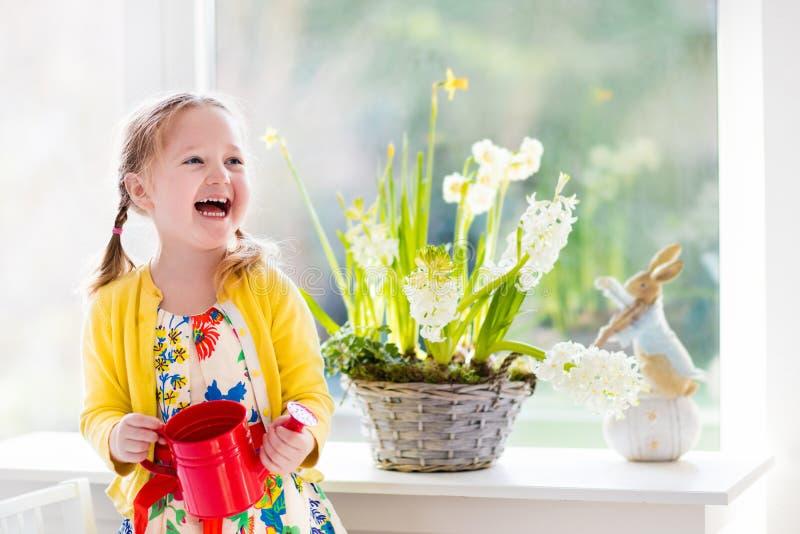 浇灌复活节花的小女孩 免版税库存图片