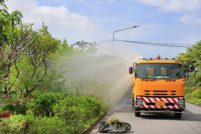 浇灌树的卡车由浪花水在公园在早晨 库存照片