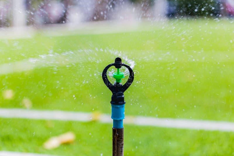 浇灌橄榄球场的洒水喷头 免版税库存照片