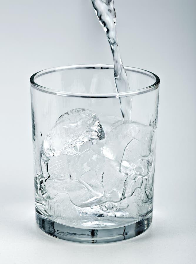 浇灌流在冰上在玻璃 库存图片