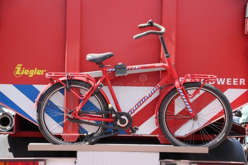 浇灌消防队员旅团的存贮卡车在wijhe的有自行车的荷兰在后面 免版税库存图片