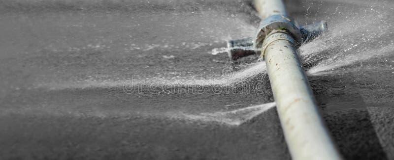 浇灌漏从在一个工业水管的孔 免版税库存图片