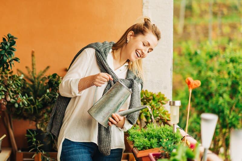 浇灌绿色植物的美女画象 库存照片