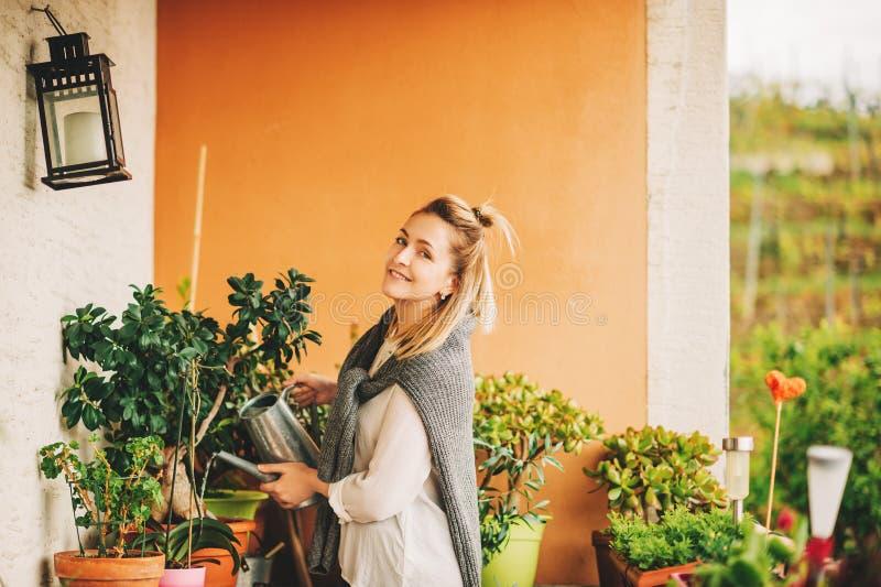 浇灌绿色植物的美女画象 库存图片