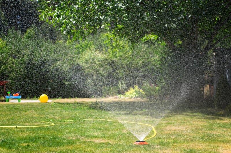 浇灌绿色草坪的灌溉系统,在一个晴朗的夏日 免版税库存照片
