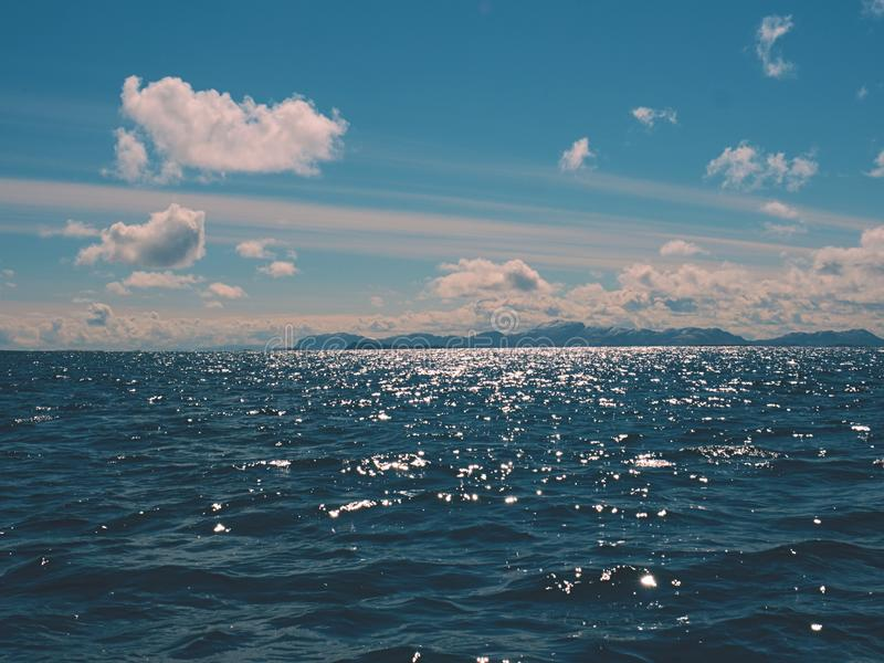 浇灌通过小的波浪,在移动与闪闪发光的五颜六色的阴影的水平面 免版税库存图片