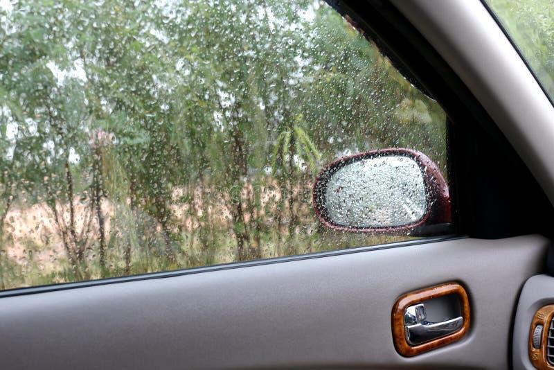 浇灌雨珠新鲜在挡风玻璃,感觉放松或孤独在汽车,清洗玻璃汽车 免版税库存图片