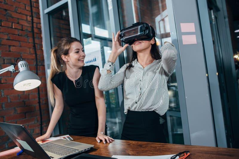 测试新的app的两位女性应用开发者为站立在现代办公室的VR耳机设计了 图库摄影