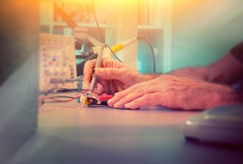 测试电子设备的前辈男性工程师的手 库存图片