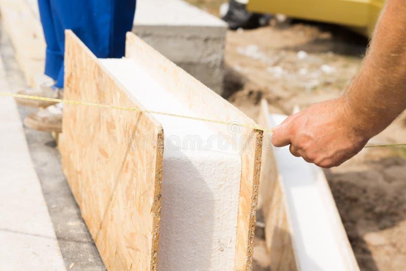 测量一个预制墙板的工作员 图库摄影