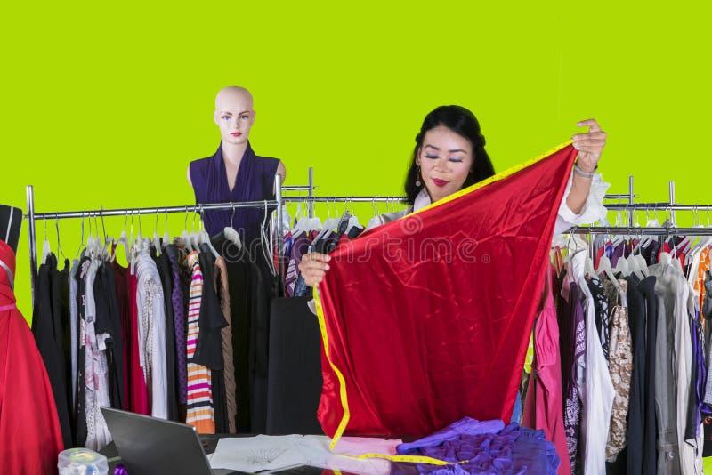 测量一种织品的俏丽的设计师在演播室 免版税库存图片