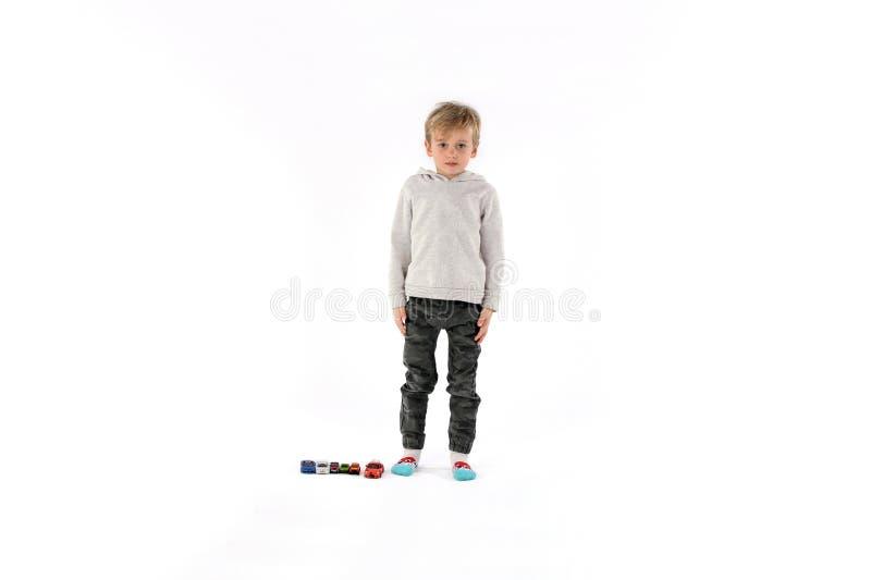测量他的与汽车玩具的逗人喜爱的儿童男孩长度由他的边 库存照片