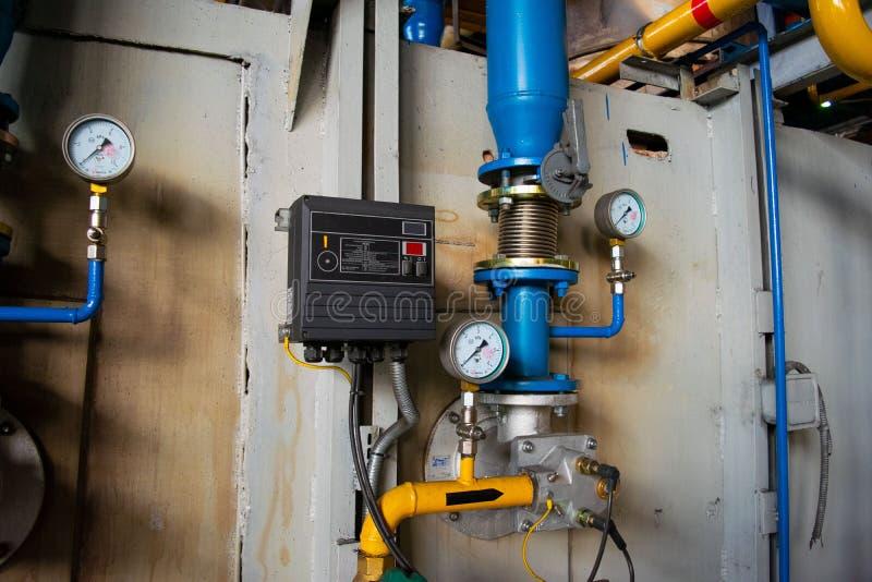 测量仪在热导管附近的锅炉室有绝缘材料涂层的 库存照片