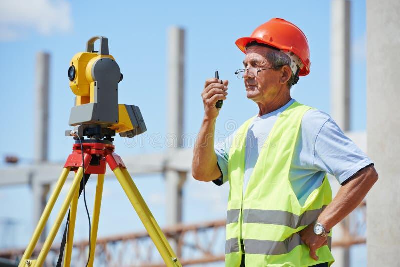 测量员与经纬仪一起使用 免版税库存图片