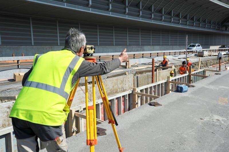 测量员做测量与经纬仪instru的工程师工作者 免版税库存照片
