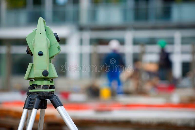 测量员在三脚架的设备经纬仪在修造的区域 免版税库存照片