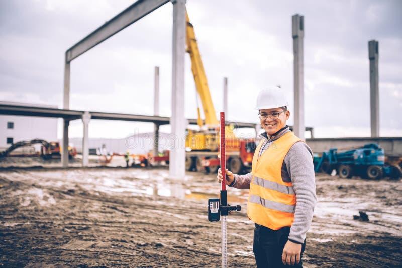 测量员工程师微笑与勘测的工具和设备的在建造场所户外,预制的水泥柱子和射线 免版税库存图片