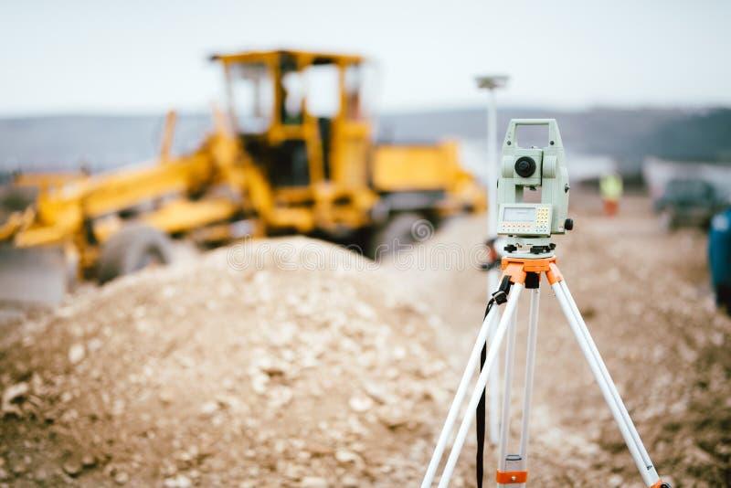 测量员户外设备GPS系统或经纬仪在高速公路建造场所 与总驻地的测量员工程学 免版税图库摄影