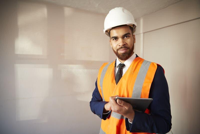 测量员画象安全帽和高可见性夹克的有数字片剂执行的议院检查的 库存图片