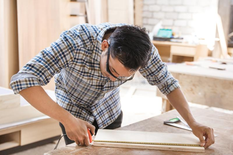 测量和标记木委员会的年轻木匠 免版税库存图片