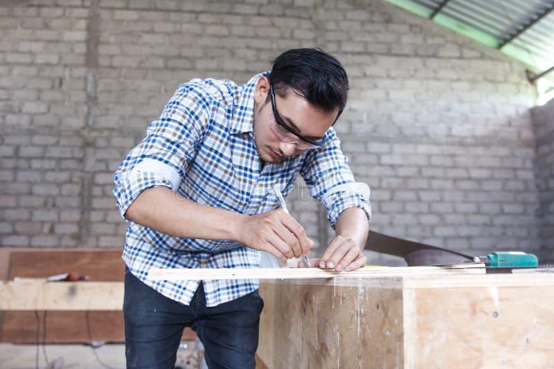 测量和标记木委员会的年轻木匠 免版税库存照片