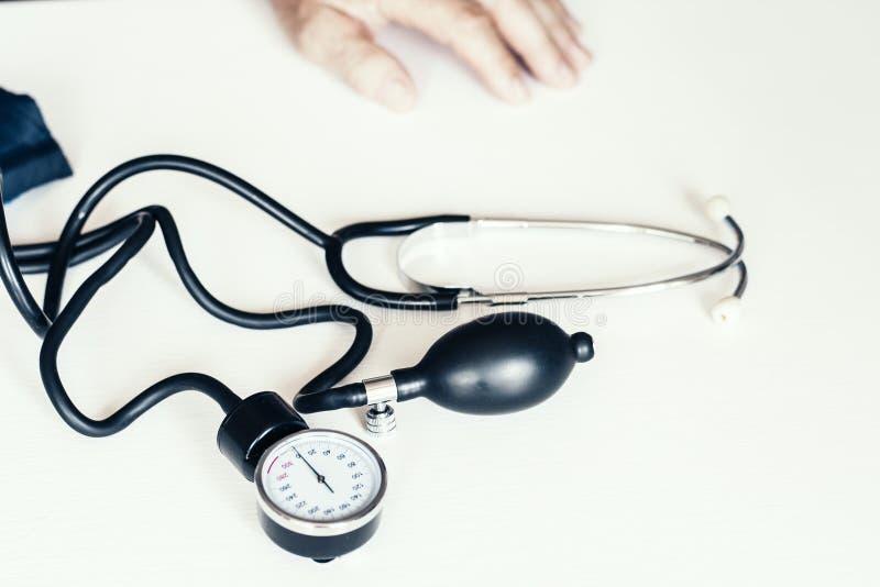 测量在白色桌上的血压的经典tonometer的片段 免版税库存图片