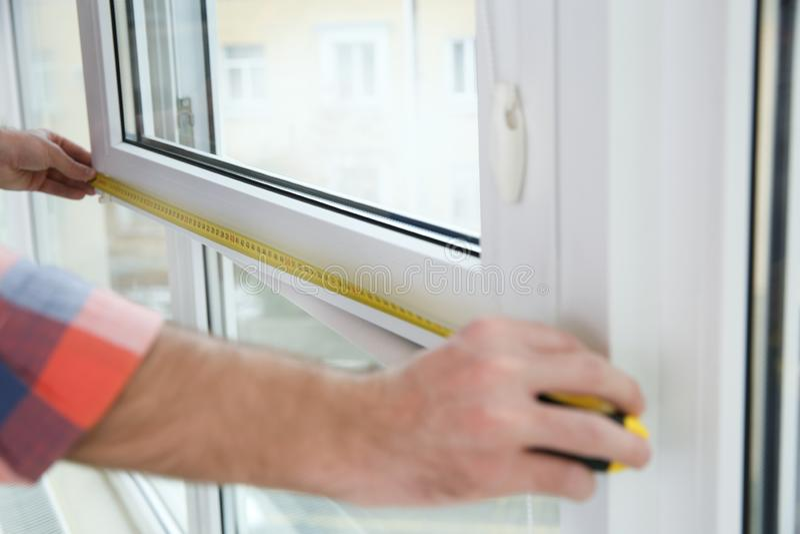 测量塑料窗口的建筑工人户内,特写镜头 免版税图库摄影