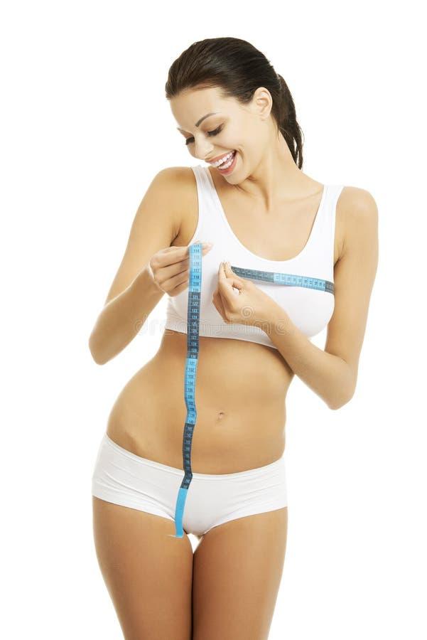 测量她的乳房的愉快的妇女 免版税库存照片