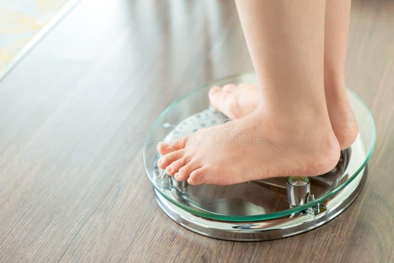 测量她的在等级的一个少妇的脚重量 免版税库存照片