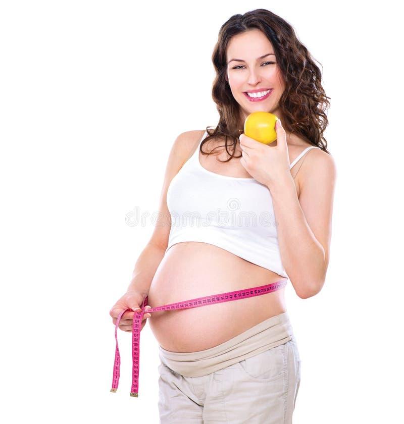 测量她的大腹部的孕妇 库存照片
