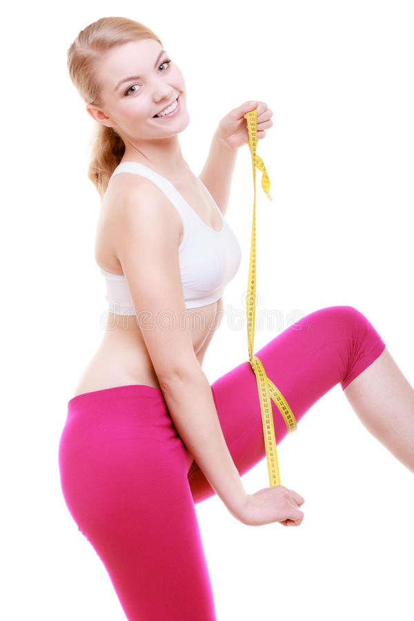 测量她的大腿的健身女孩运动的妇女被隔绝 免版税库存图片
