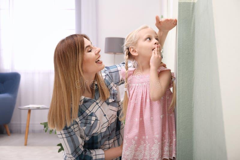 测量她的女儿` s高度的少妇 库存图片