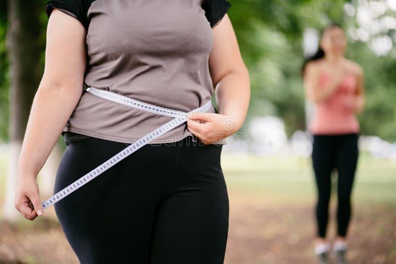 测量她的腰围的肥胖妇女 免版税库存照片