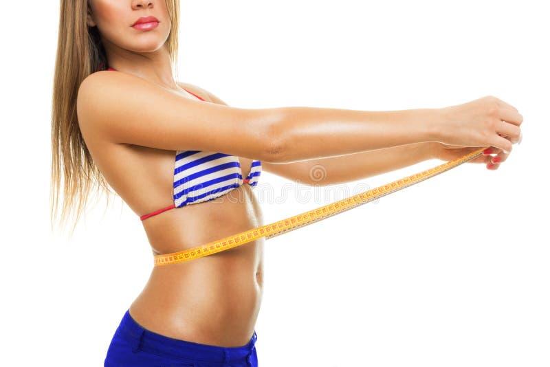 测量她的腰部佩带的比基尼泳装的适合的少妇 免版税图库摄影