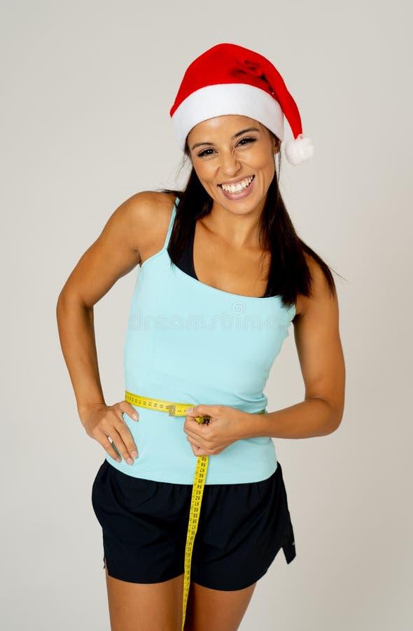 测量她的腰部感觉的圣诞老人帽子的适合的少妇愉快和陈列胜利和好姿态 免版税库存照片