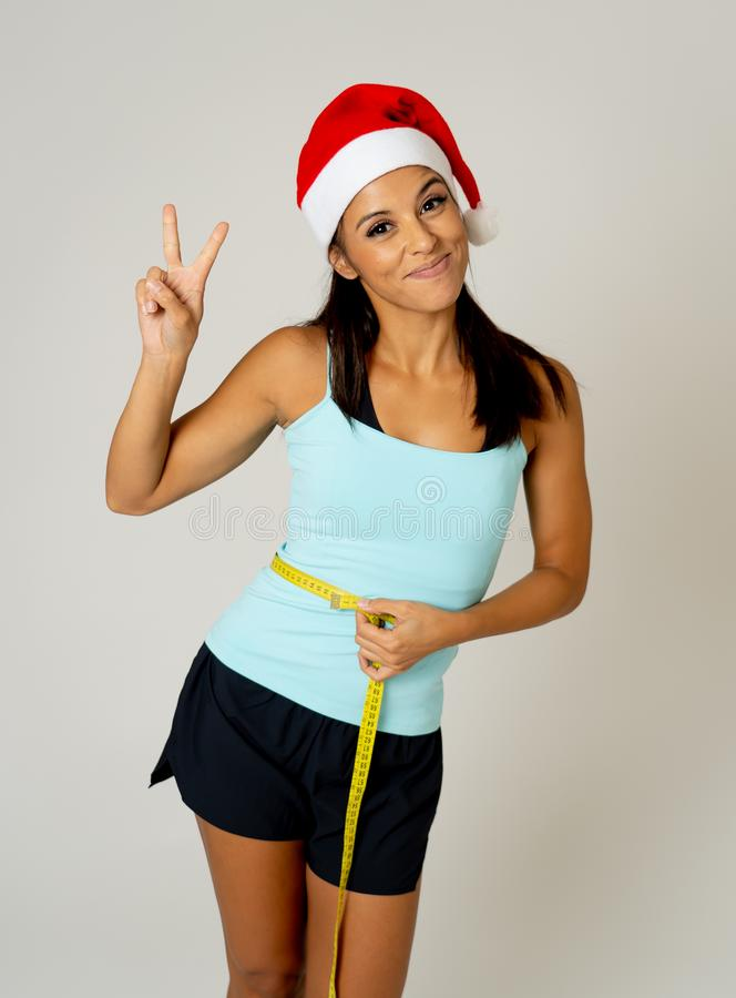 测量她的腰部感觉的圣诞老人帽子的适合的少妇愉快和陈列胜利和好姿态 免版税图库摄影