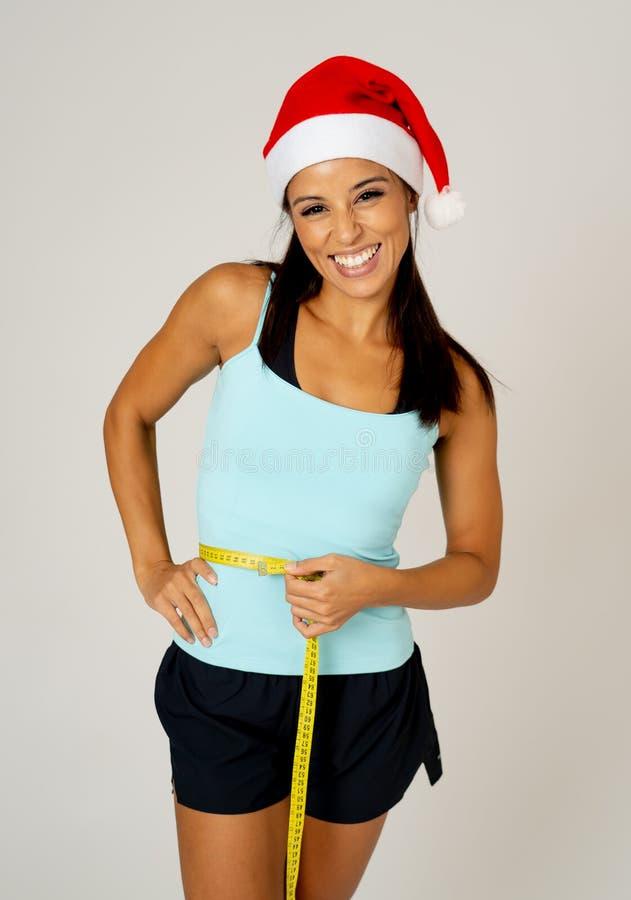 测量她的腰部感觉的圣诞老人帽子的适合的少妇愉快和陈列胜利和好姿态 免版税库存图片