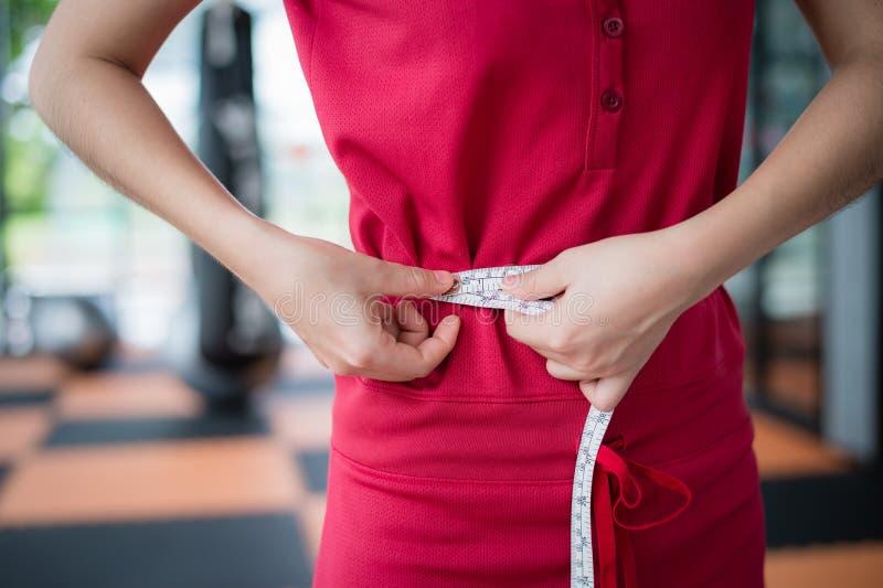 测量她的腰部的妇女用途测量的磁带在锻炼以后在 免版税库存图片