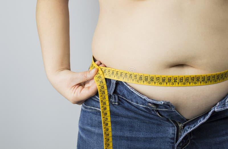 测量她的腰部的肥胖妇女 免版税图库摄影