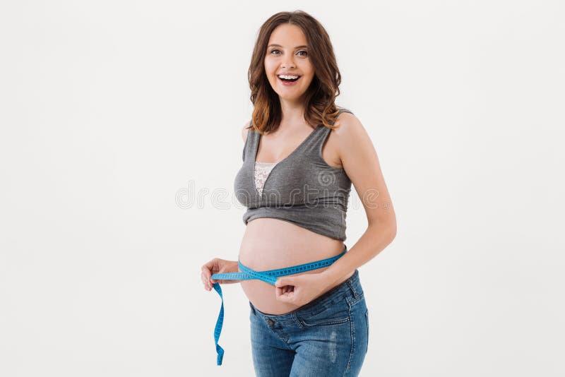 测量她的腹部的一名愉快的激动的孕妇的画象 图库摄影