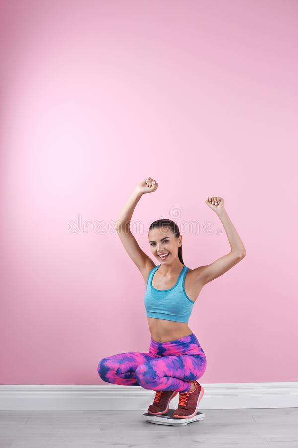 测量她的重量的愉快的少妇使用标度临近颜色墙壁 图库摄影