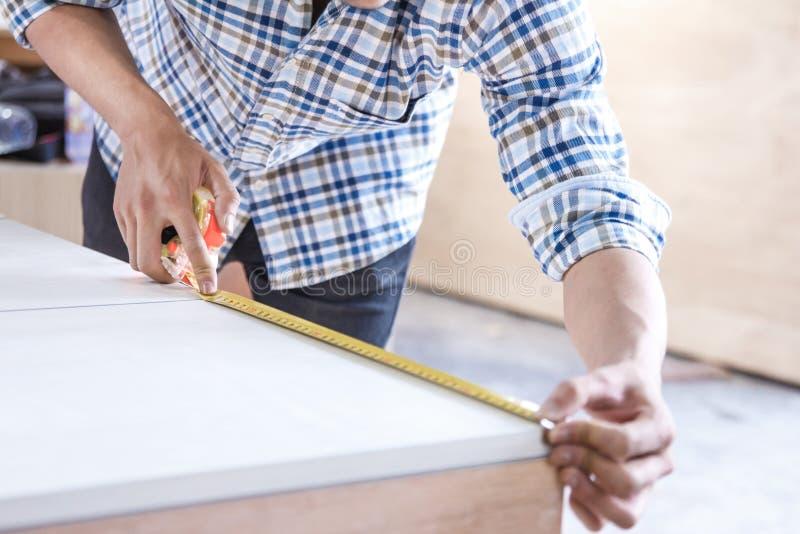测量家具的年轻木匠 免版税库存图片