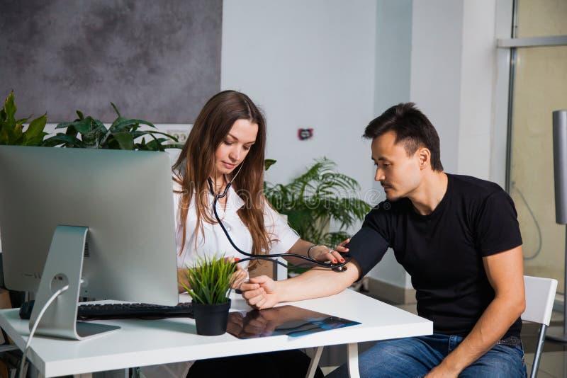 测量患者的女性医生动脉血压力在诊所 库存照片