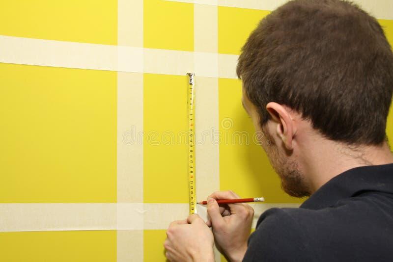 测量有修稿带的人内墙 免版税库存照片