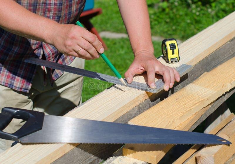 测量木板条的男性手 免版税库存照片
